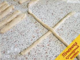 11) Через 10 минут жгутики станут попышней, тесто нагреется. Смазанными растительным маслом руками раскатать жгутики в длинные шнуры (желательно одинаковые) толщиной в палец. Теперь начинаем плести Пита майзе, булочки из дрожжевого теста. Возьмите 2 шнура из теста, положите их крест-накрест.