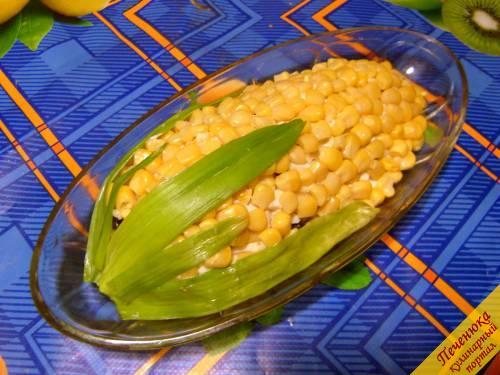 6) Украсить салат, оформив его под початок зрелой кукурузы. Для этого по всей поверхности салата выложить оставленные зернышки кукурузы. Взять несколько перышек зеленого лука, разрезать их с одной стороны и распластать, чтобы получился широкий лист, кончики заострить ножницами. Внутреннюю сторону лука смазать майонезом, чтобы лист не сворачивался, а «приклеился» к «початку». Имеет смысл подержать салат пару часов в холодильнике, тогда он будет особенно вкусным.