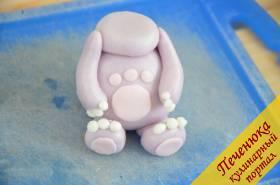 8) Соединить детали, слегка смазав места соединения водой. На лапках сделать пальчики из белой мастики. А также из розовой мастики сделать пятки и животик.