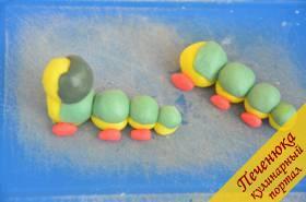 12) Помимо Лунтика я еще делала гусениц – Вупсеня и Пупсеня. Для туловища необходимо скатать желтые и зеленые шарики, а затем соединить их немного приплюснув, так чтобы получился один шарик. Из красной мастики сделать лапки. Чтобы сделать верхнюю часть туловища необходимо скатать желтый шарик. Затем поверх него обернуть мастику темно-зеленого цвета – это будущая жилетка.