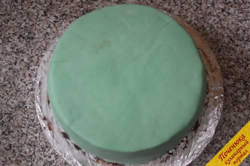 18) Для покрытия торта мастику покрасить в зеленый цвет. Стол присыпать сахарной пудрой и раскатать ее толщиной в 3-5 мм. Намотать пласт на скалку, а затем быстро перенести на поверхность торта, аккуратно выравнивая со всех сторон. Мастика очень похожа на пластилин, поэтому довольно легко выравнивается и обтягивается. Лишние части мастики аккуратно срезать.