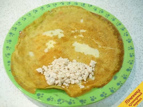 5) Перекладываем один блинчик на плоское блюдо, на край укладываем столовую ложку мясной начинки и заворачиваем блинчик конвертиком.